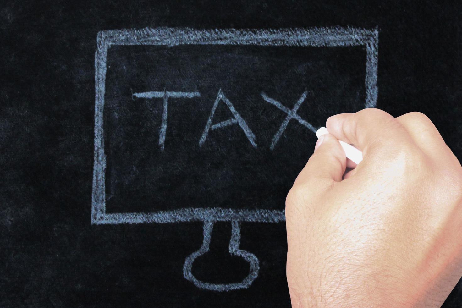 hand skriva skatteord på svarta tavlan foto