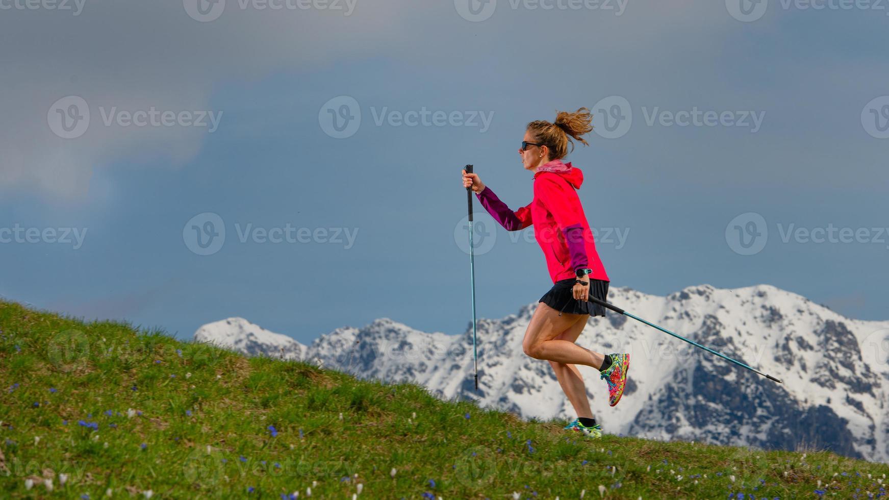 stavgång och spårlöpning en tjej med pinnar på fjällbrasan med snöig bakgrund foto