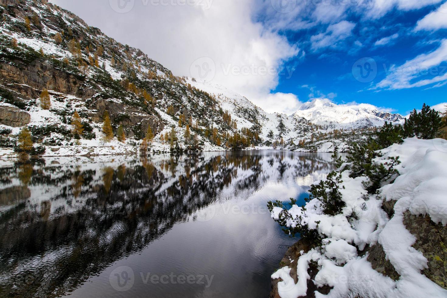 berg och alpinsjö med snöfall foto