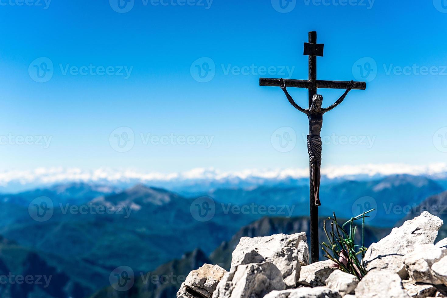 litet järnkrucifix på toppen av ett berg foto