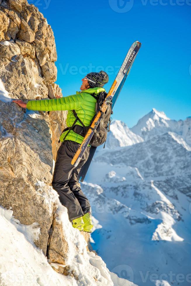 skidåkare klättraren med skidor på ryggsäcken foto