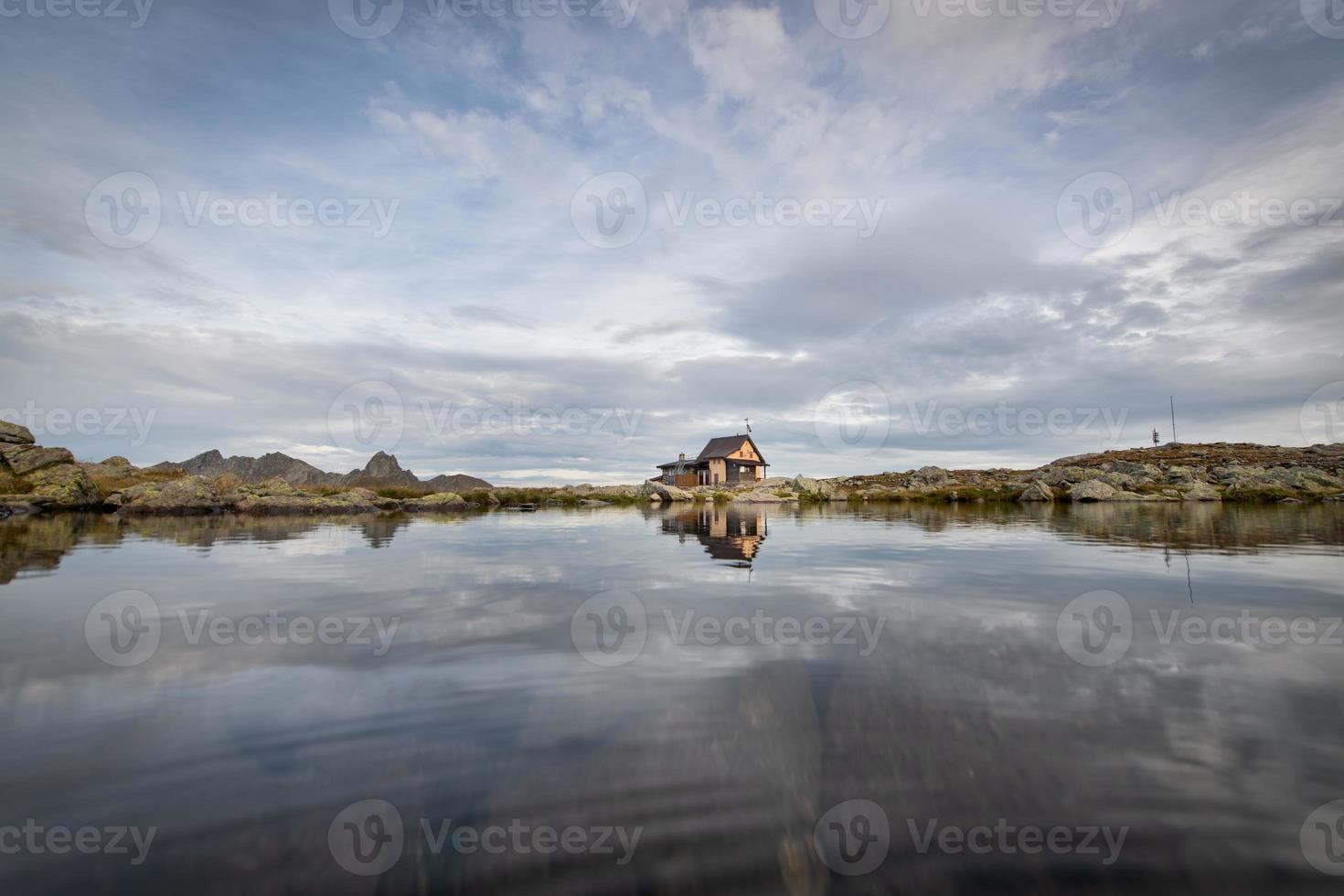 liten eremit i bergen nära en sjö foto