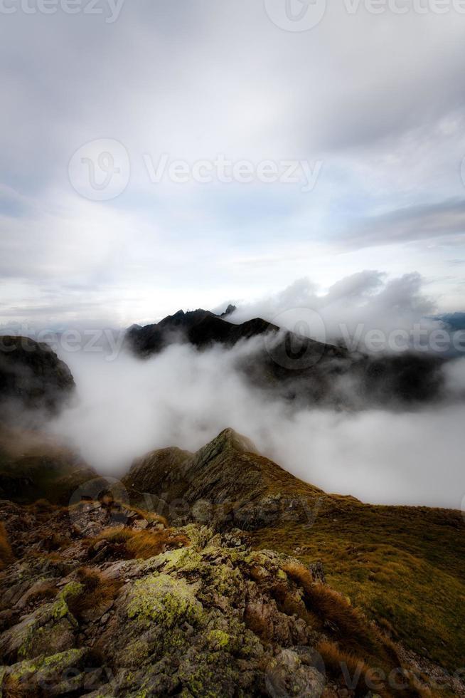 bergslandskap med moln runt topparna foto