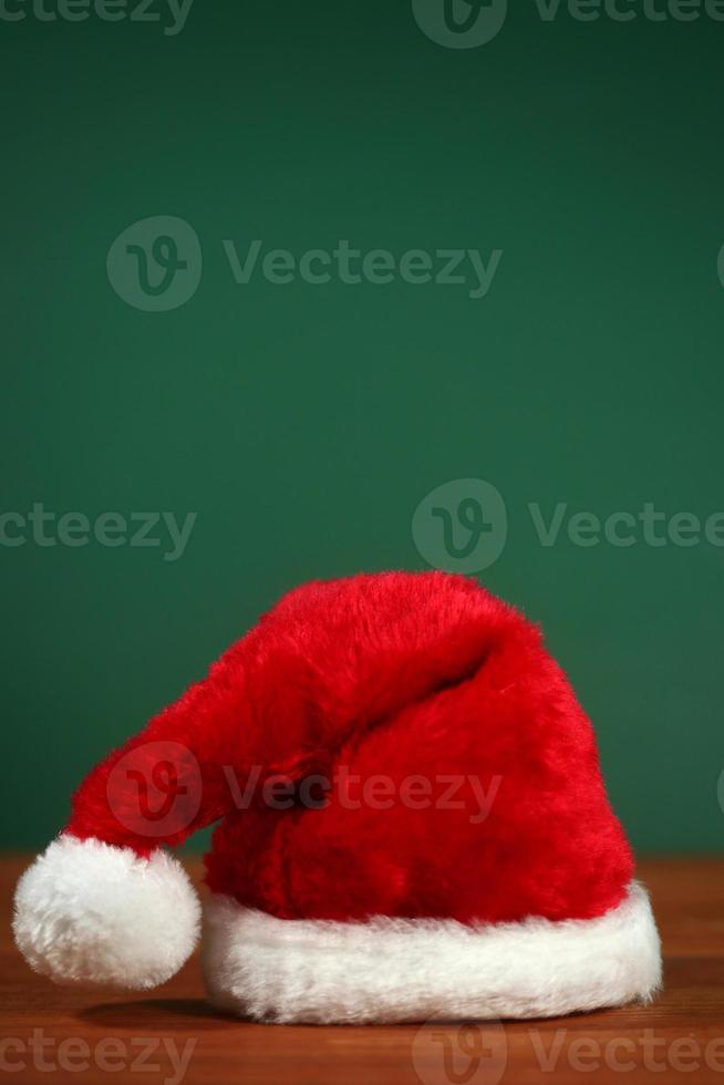 röd santa hatt med kopia utrymme på grön och trä bakgrund foto