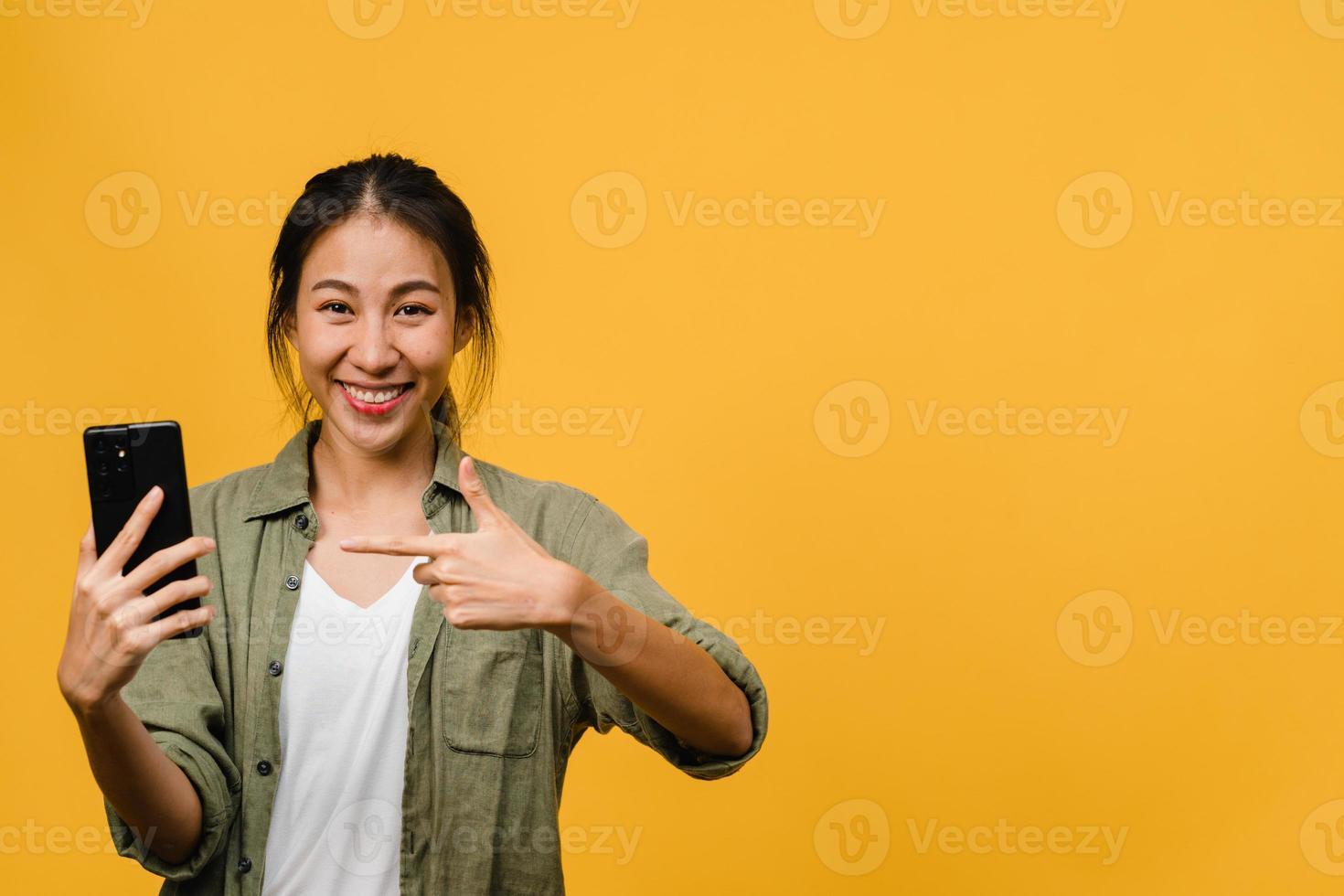ung asiatisk dam som använder mobiltelefon med glada uttryck, visar något fantastiskt på tomt utrymme i vardagsduk och tittar på kameran isolerad över gul bakgrund. ansiktsuttryck koncept. foto