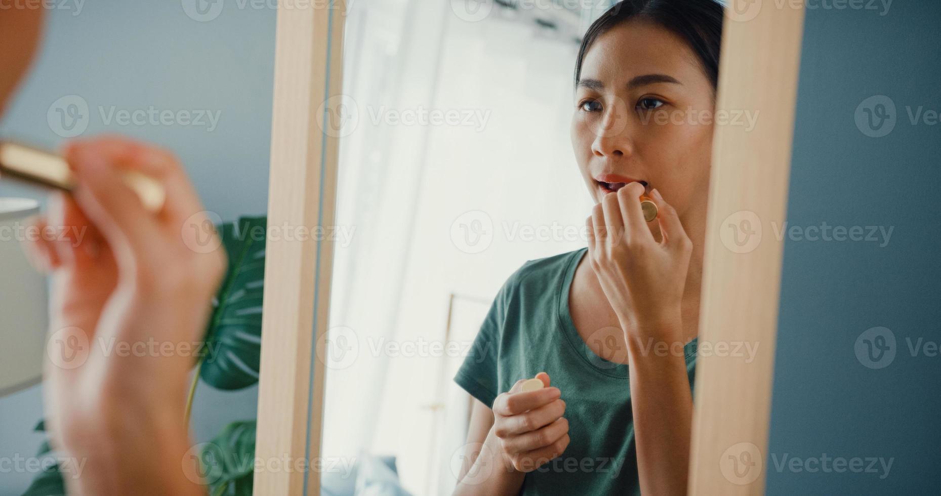 vacker asiatisk dam med avslappnad trasa satte läppstift på läpparna framför spegeln i sovrummet hemma på morgonen innan de gick ut utanför. leende ung kvinna som sminkar sig och tittar på spegeln. foto
