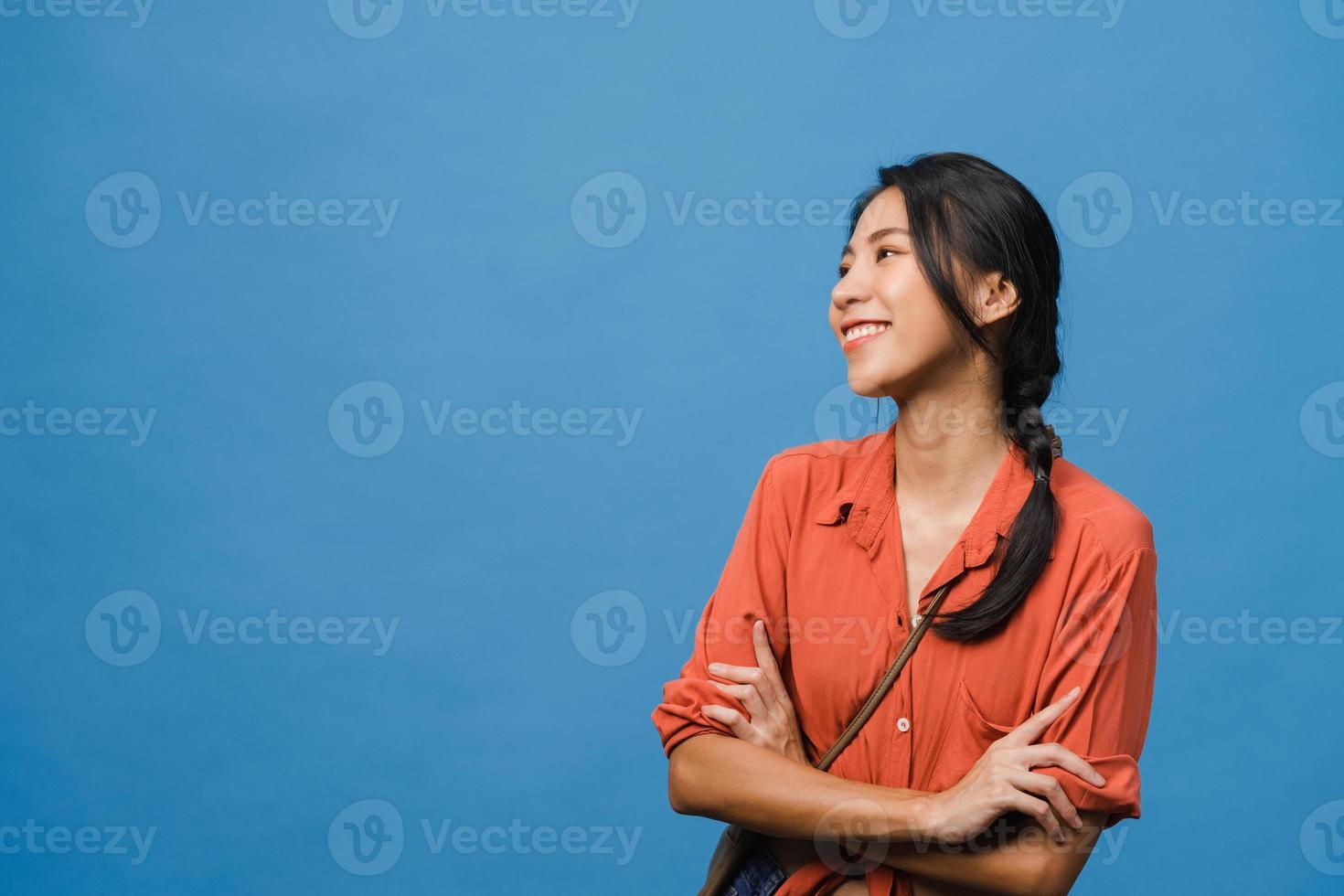 porträtt av ung asiatisk dam med positivt uttryck, korsade armar, le brett, klädd i avslappnad trasa över blå bakgrund. glad förtjusande glad kvinna jublar över framgång. ansiktsuttryck koncept. foto