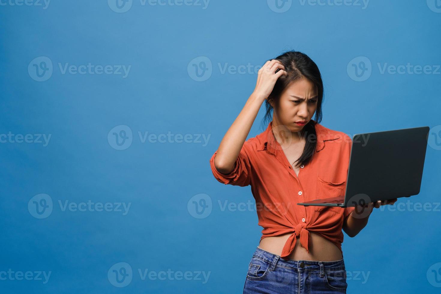 ung asiatisk dam med bärbar dator med negativt uttryck, upphetsad skrik, gråta känslomässigt arg i avslappnad trasa och stå isolerad på blå bakgrund med tomt kopieringsutrymme. ansiktsuttryck koncept. foto
