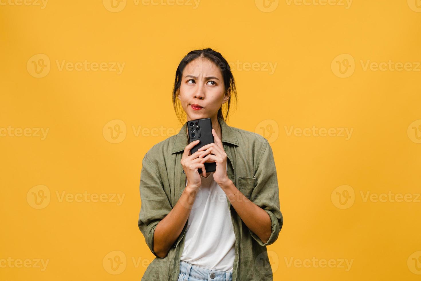 tänkande drömmer ung asiatisk dam med telefon med positivt uttryck, klädd i avslappnad trasa som känner lycka och står isolerad på gul bakgrund. glad förtjusande glad kvinna jublar över framgång. foto