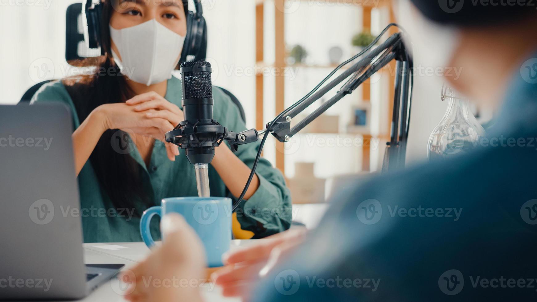 asien tjej radio värd spela in podcast använda mikrofon ha på sig hörlurar intervju gästinnehåll bära mask skydda viruskonversation prata och lyssna i hennes rum. podcast hemifrån, coronavirus -karantän. foto