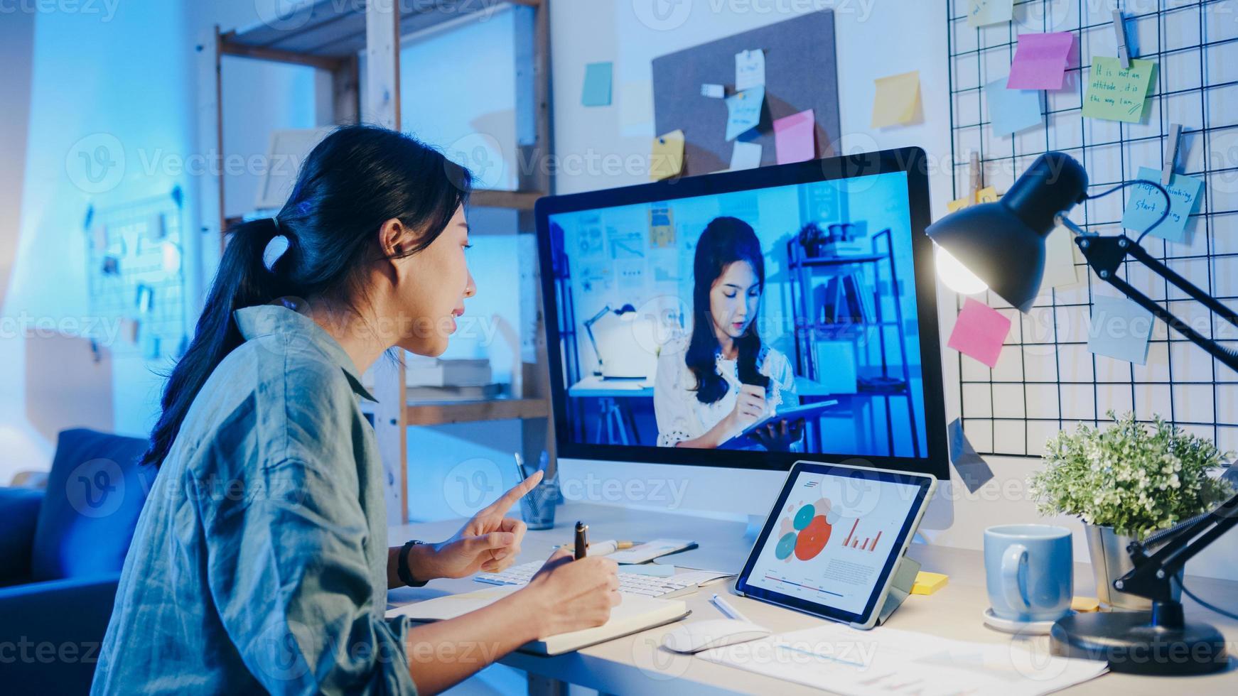 asiatisk affärskvinna som använder skrivbordssamtal med kollegor om planering i videosamtalsmöte i vardagsrummet. arbeta från huset överbelastning på natten, distansarbete, social distansering, karantän för coronavirus. foto