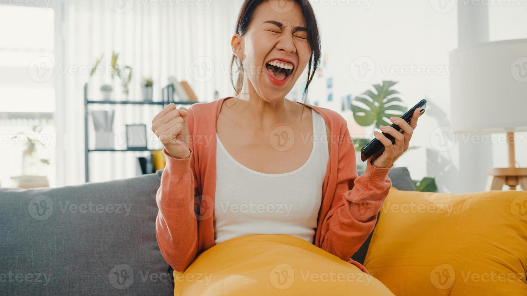vacker asiatisk dam sitter i soffan känns spännande med bra nyheter hemma. framgångsintervju, examen prestation, dejting match acceptera, start kredit godkänna, godkänt test, arbetsgivare acceptera jobb koncept. foto