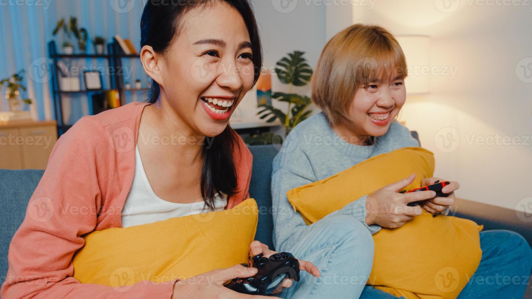 lesbisk lgbtq kvinnor par spela videospel hemma. ung asiatisk dam med trådlös handkontroll som har roligt lyckligt ögonblick på soffan i vardagsrummet på natten. de har en fantastisk och rolig tid firar semester. foto