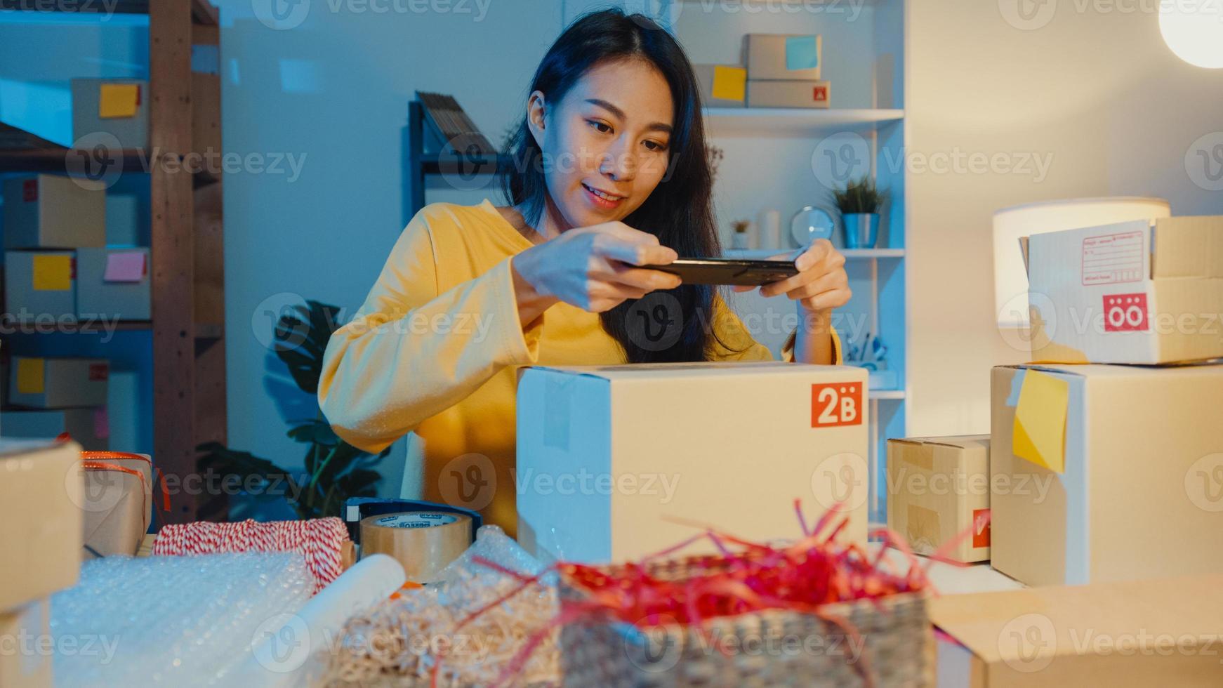 ung asiatisk kvinna använder smartphone ta streckkodsbild på paketprodukt för leverans till kund på hemmakontor på natten. småföretag, online marknadsföring, livsstil frilans koncept. foto