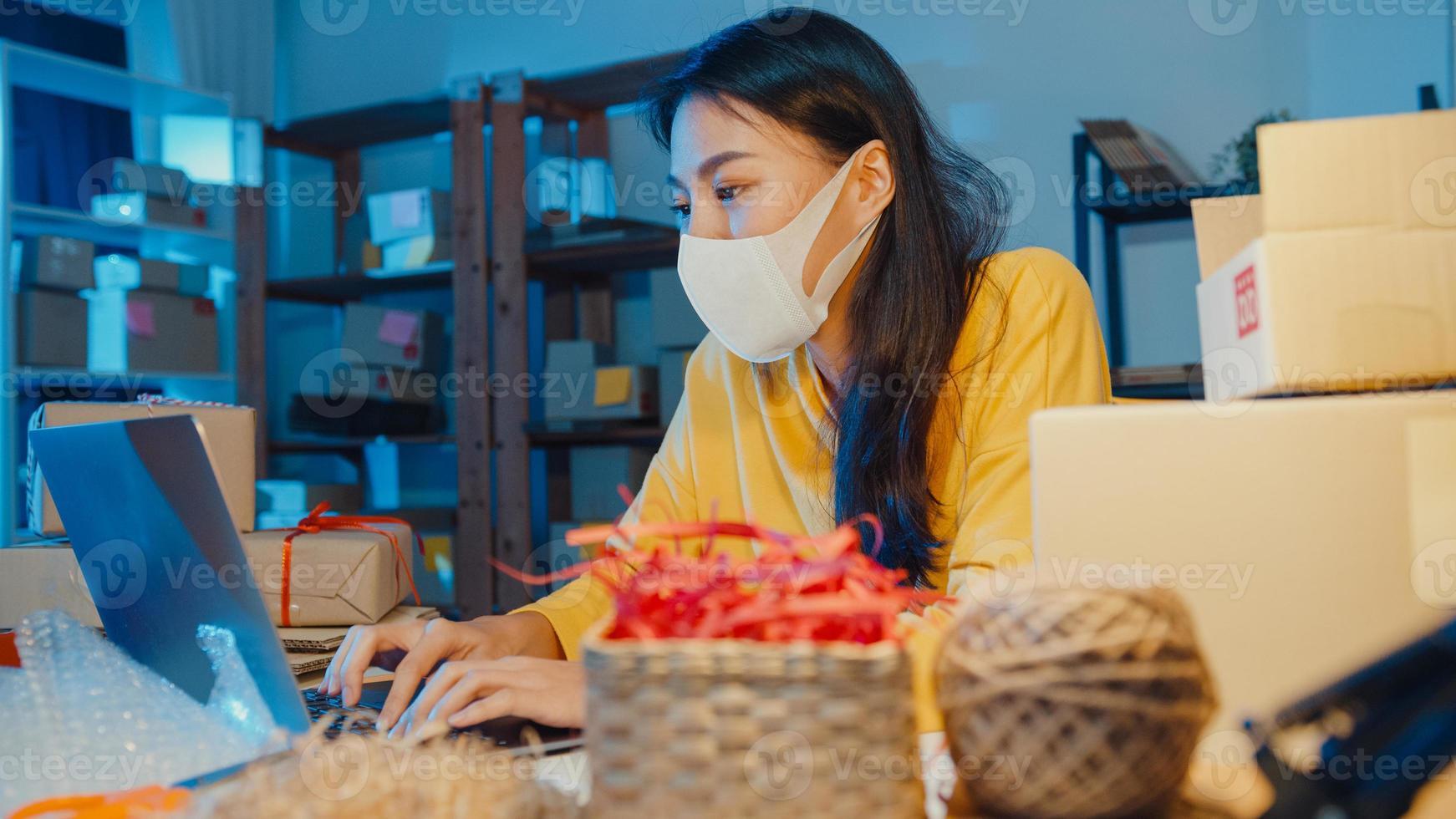 ung asiatisk affärskvinna bära ansiktsmask kontrollera inköpsorder och svara klient inkorg chatt på bärbar dator på hemmakontor på natten. småföretagare, onlinemarknadsleverans, livsstil frilansande koncept. foto