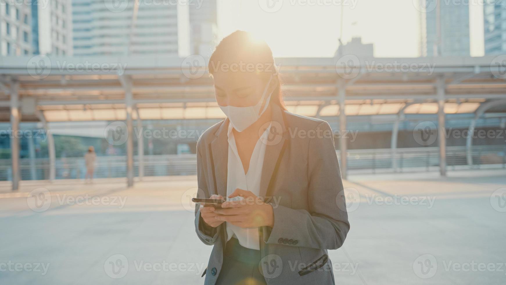 ung asiatisk affärskvinna i mode kontorkläder bär medicinsk ansiktsmask med telefon medan hon går ensam utomhus i stad. företag på gång, social distansering för att förhindra spridning av covid-19-konceptet. foto