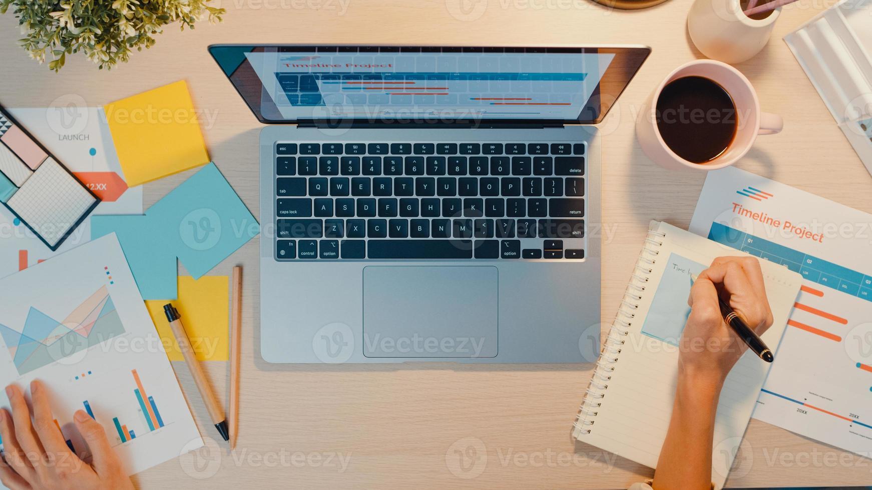 ovanifrån av ung asien affärsframe frilans fokus på bärbar dator skriva kalkylblad finans diagram kontot diagram marknadsplan på kontorsnatt. arbeta hemifrån, på distans, distansutbildning coronavirus -koncept foto