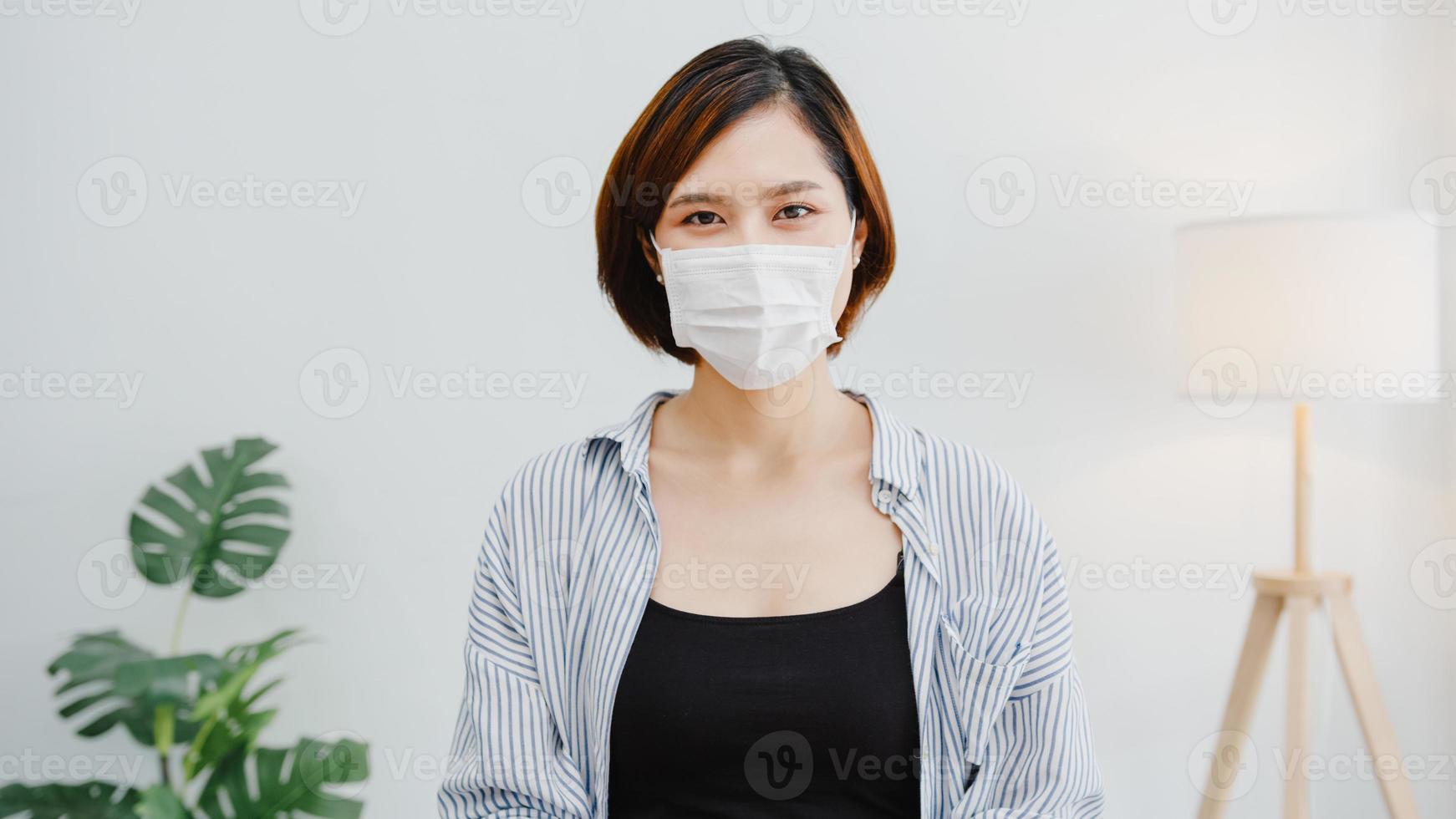 asiatisk affärskvinna bär ansiktsmask social distansering i situation för virusförebyggande tittar på kameran leende under kirurgisk mask tillbaka till jobbet i kontorsarbetsytan. livsstil efter corona -virus. foto