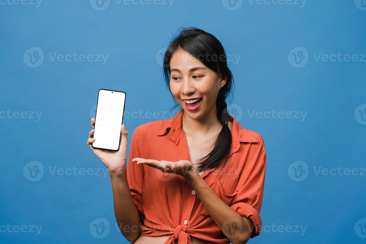 ung asiatisk dam visar tom smartphone -skärm med positivt uttryck, ler brett, klädd i vardagskläder som känner lycka på blå bakgrund. mobiltelefon med vit skärm i kvinnlig hand. foto