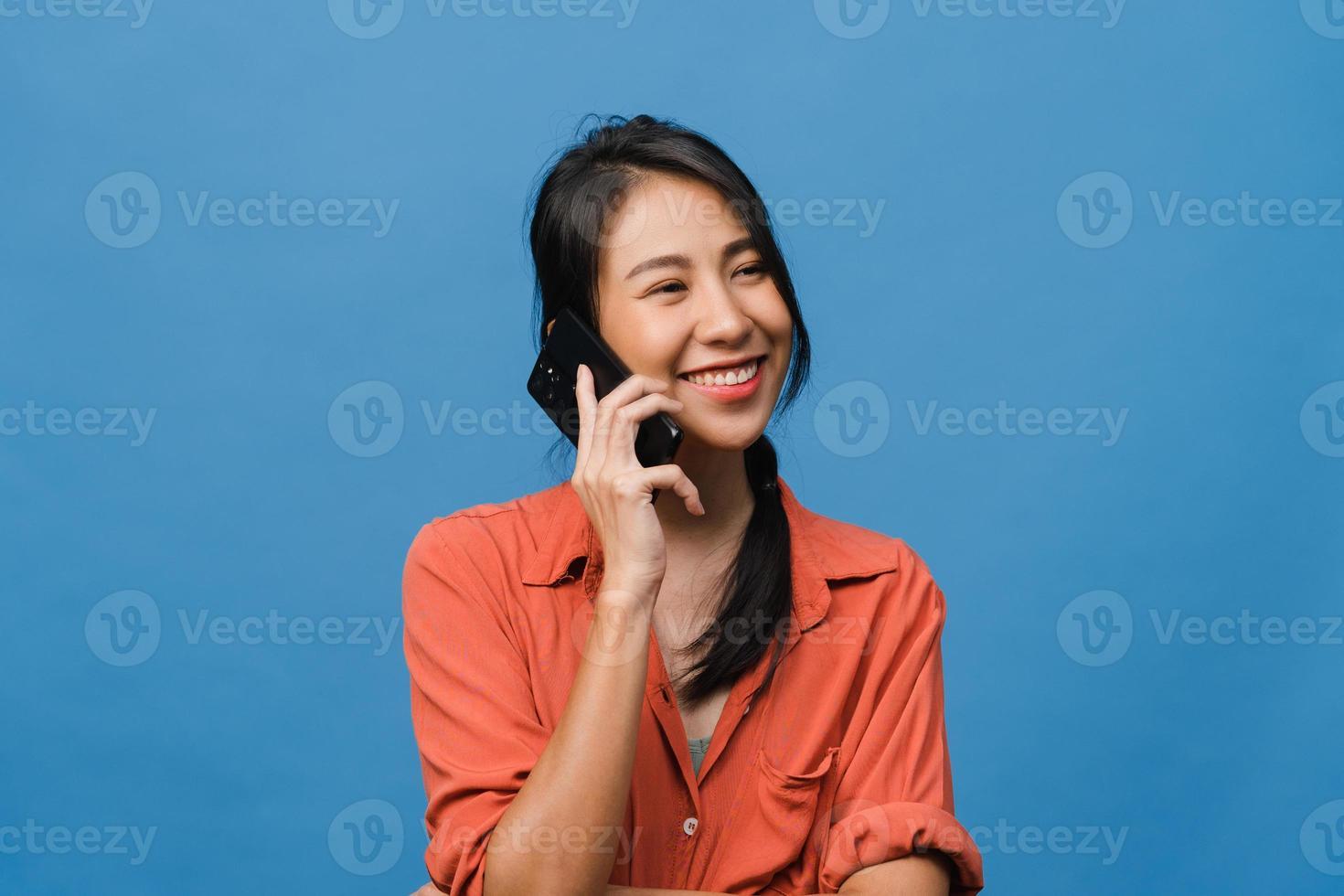 ung asiatisk dam pratar i telefon med positivt uttryck, ler brett, klädd i vardagskläder som känner lycka och står isolerad på blå bakgrund. glad förtjusande glad kvinna jublar över framgång. foto