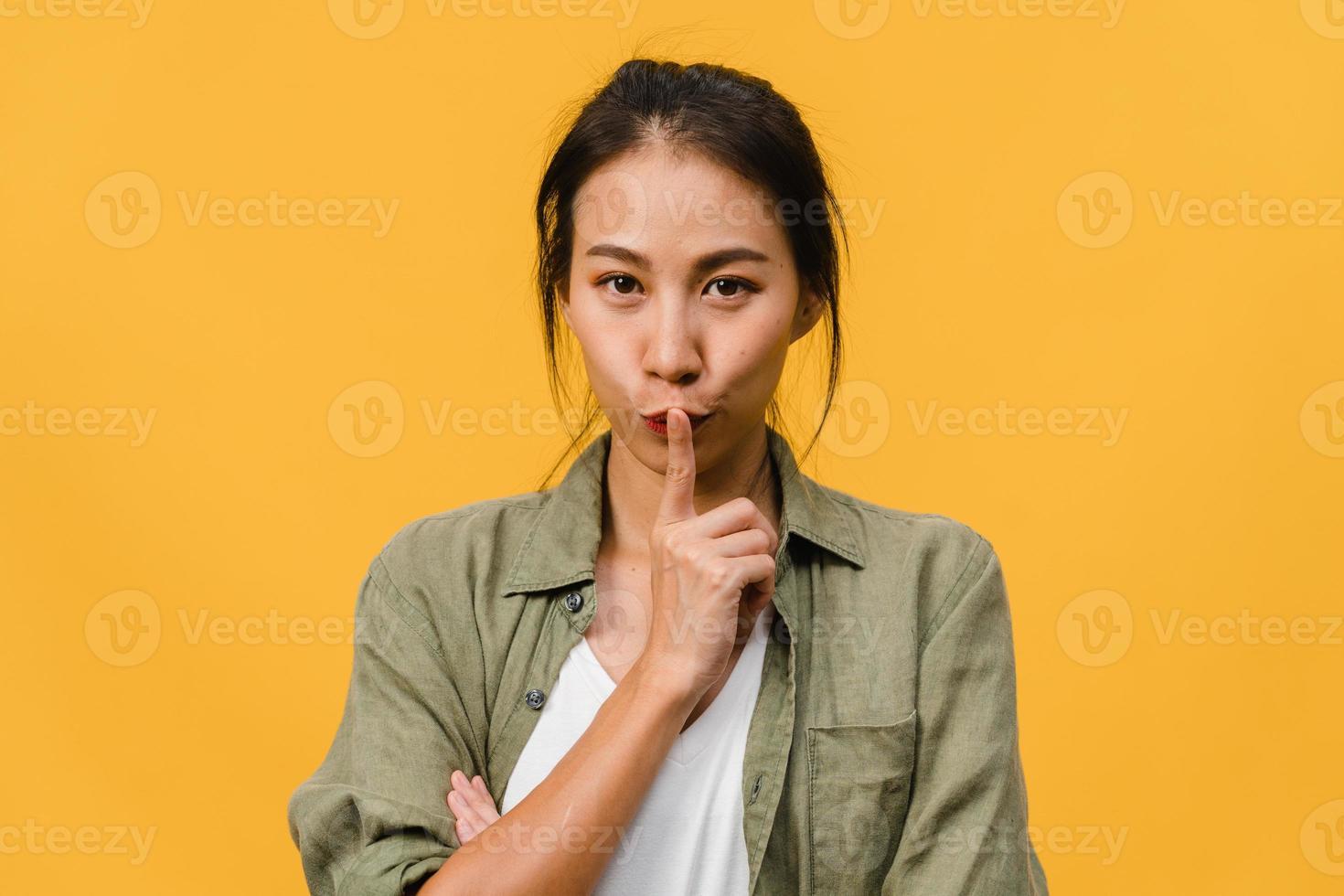 porträtt av ung asiatisk dam med positivt uttryck, tänker på kommande helgdagar, klädd i vardagskläder och tittar på kameran över gul bakgrund. glad förtjusande glad kvinna jublar över framgång. foto