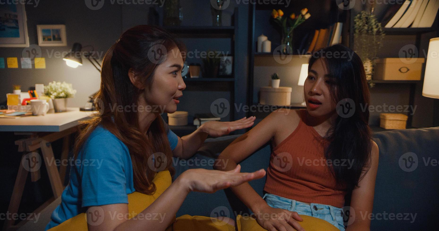 glada attraktiva asiatiska kvinnor med avslappnad koppla av i soffchatten prata tillsammans om sitt liv och relationskvaller i vardagsrummet hemma natt. flickvänner rumskamrat bo i sovsal tillsammans. foto