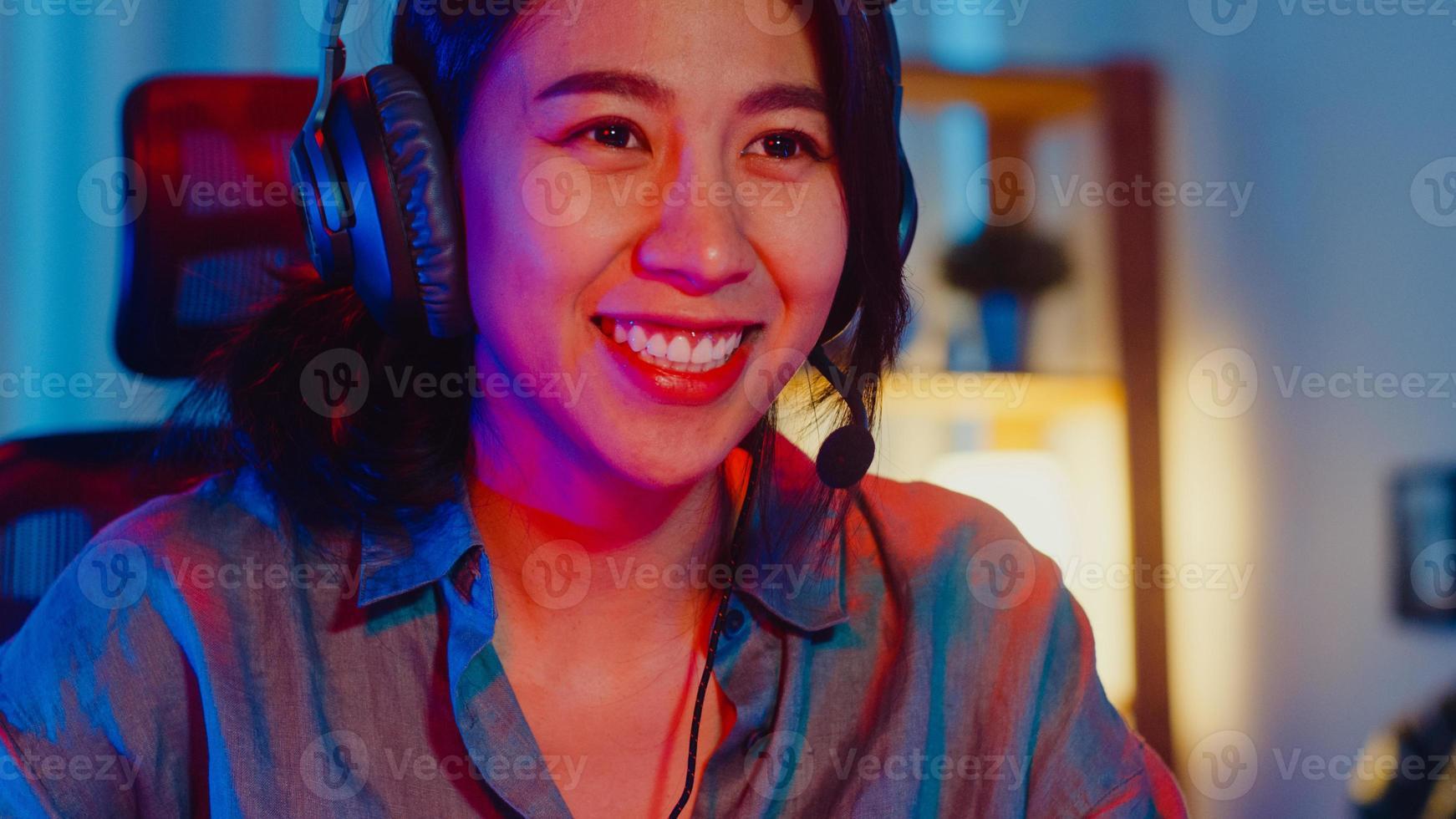glad asien professionell tjejspelare ha på sig hörlurar spela videospel färgglada neonljusdatorer i vardagsrummet hemma. esport -strömmande spel online, hemmakarantänaktivitetskoncept. foto
