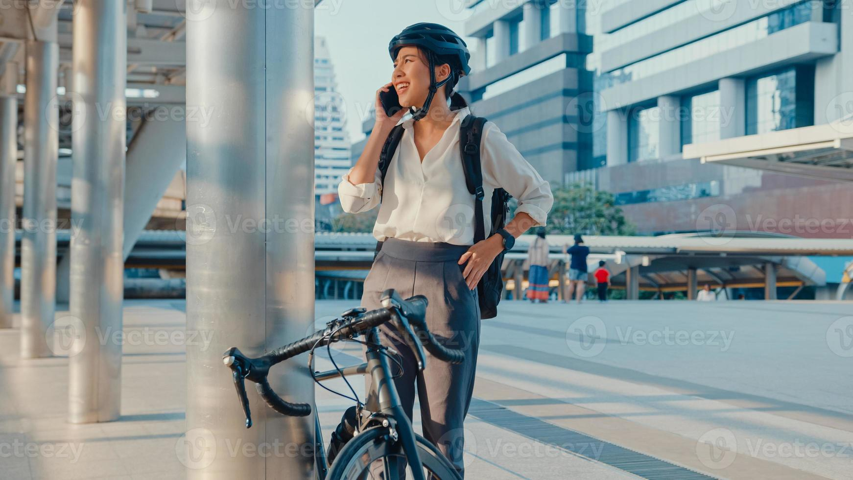 asiatisk affärskvinna med ryggsäck plocka upp mobiltelefon prata leende klocka smartwatch i stadsgatan jobba på kontoret. sportflicka använder telefonaffärer. pendla till jobbet med cykel, affärspendlare i staden. foto
