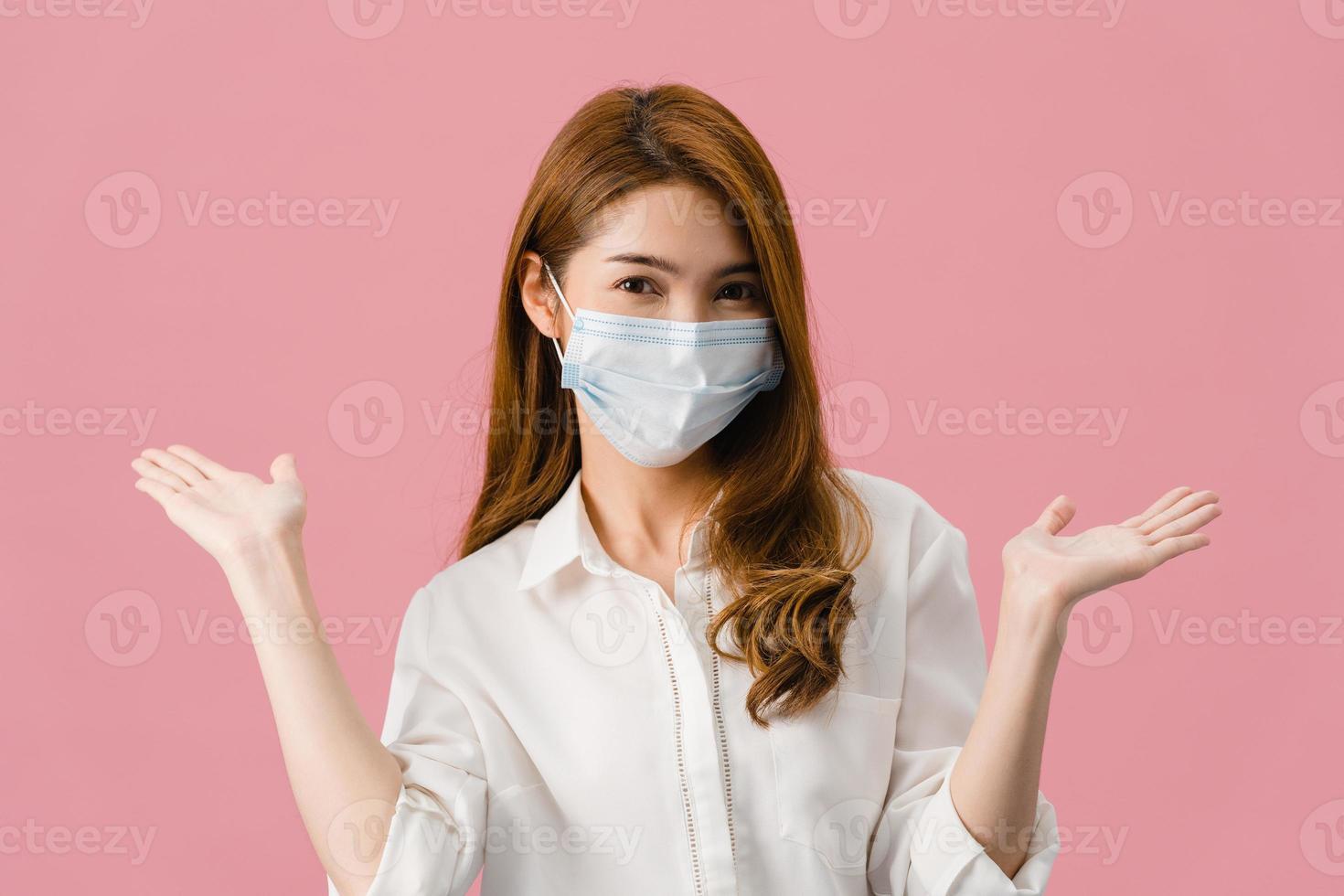 ung asiatisk tjej som bär medicinsk ansiktsmask som visar fredstecken, uppmuntra med klädd i vardaglig trasa och titta på kameran isolerad på rosa bakgrund. social distansering, karantän för corona. foto