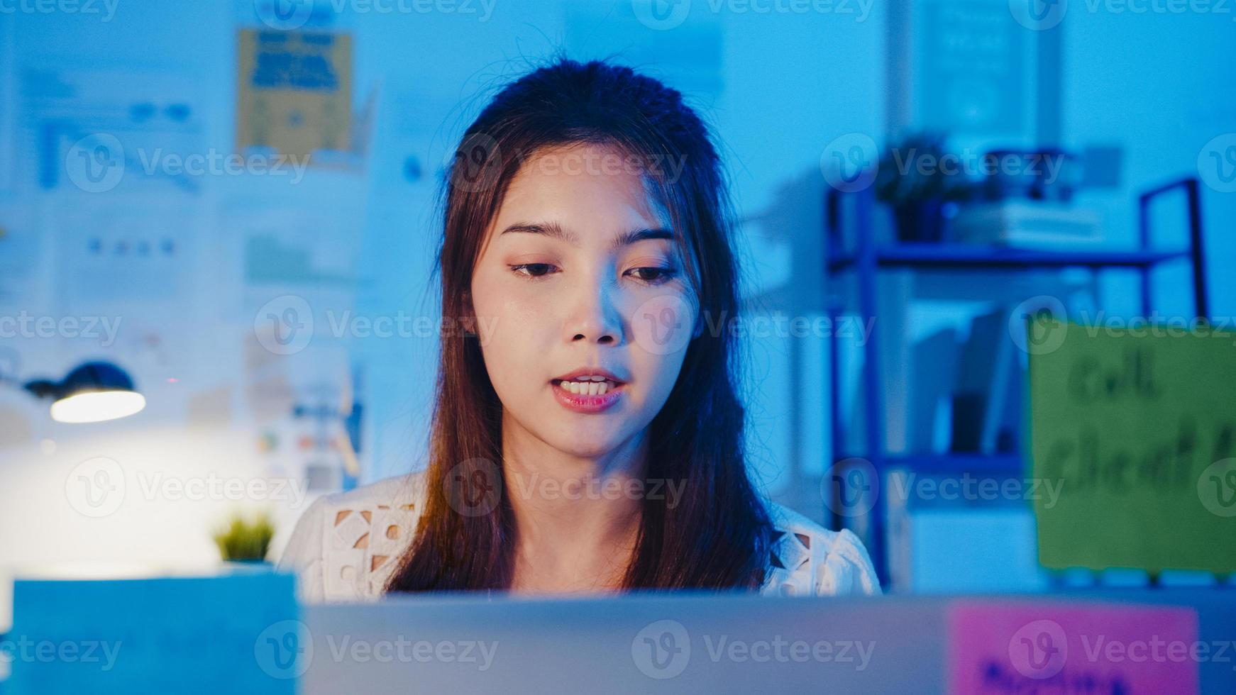 asiatisk affärskvinna social distansering i nya normala för virusförebyggande tittar på kamerapresentation för kollega om planering i videosamtal medan du arbetar på kontorsnatt. livsstil efter coronaviruset. foto