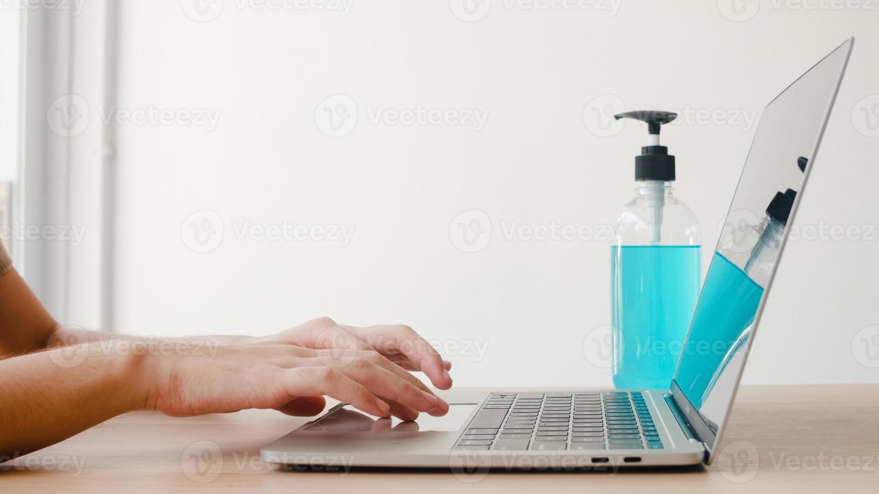 asiatisk kvinna som använder alkohol gel desinfektionsmedel tvätta händerna före arbete på bärbar dator för att skydda coronaviruset. kvinnor pressar alkohol för att städa för hygien när social distans stannar hemma och självkarantän. foto