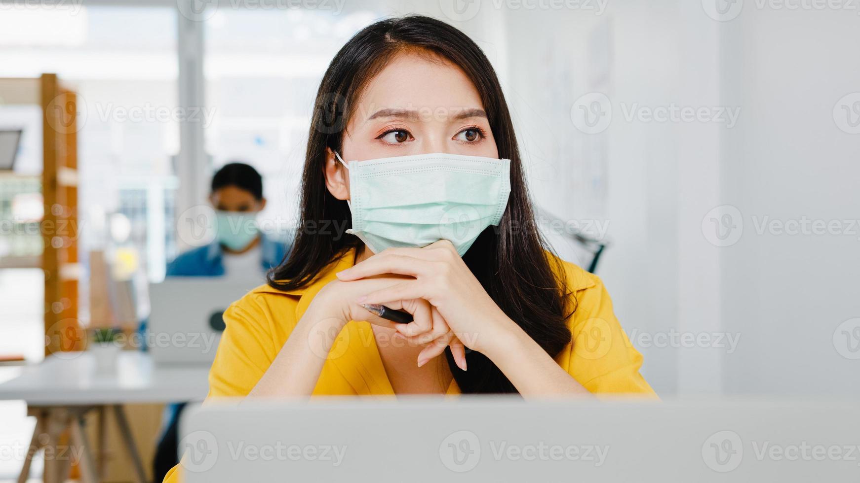 frilansande asiatiska kvinnor bär ansiktsmask med hjälp av laptop hårt arbete på nya vanliga hemmakontor. överbelastning från huset, självisolering, social distansering, karantän för förebyggande av corona -virus. foto