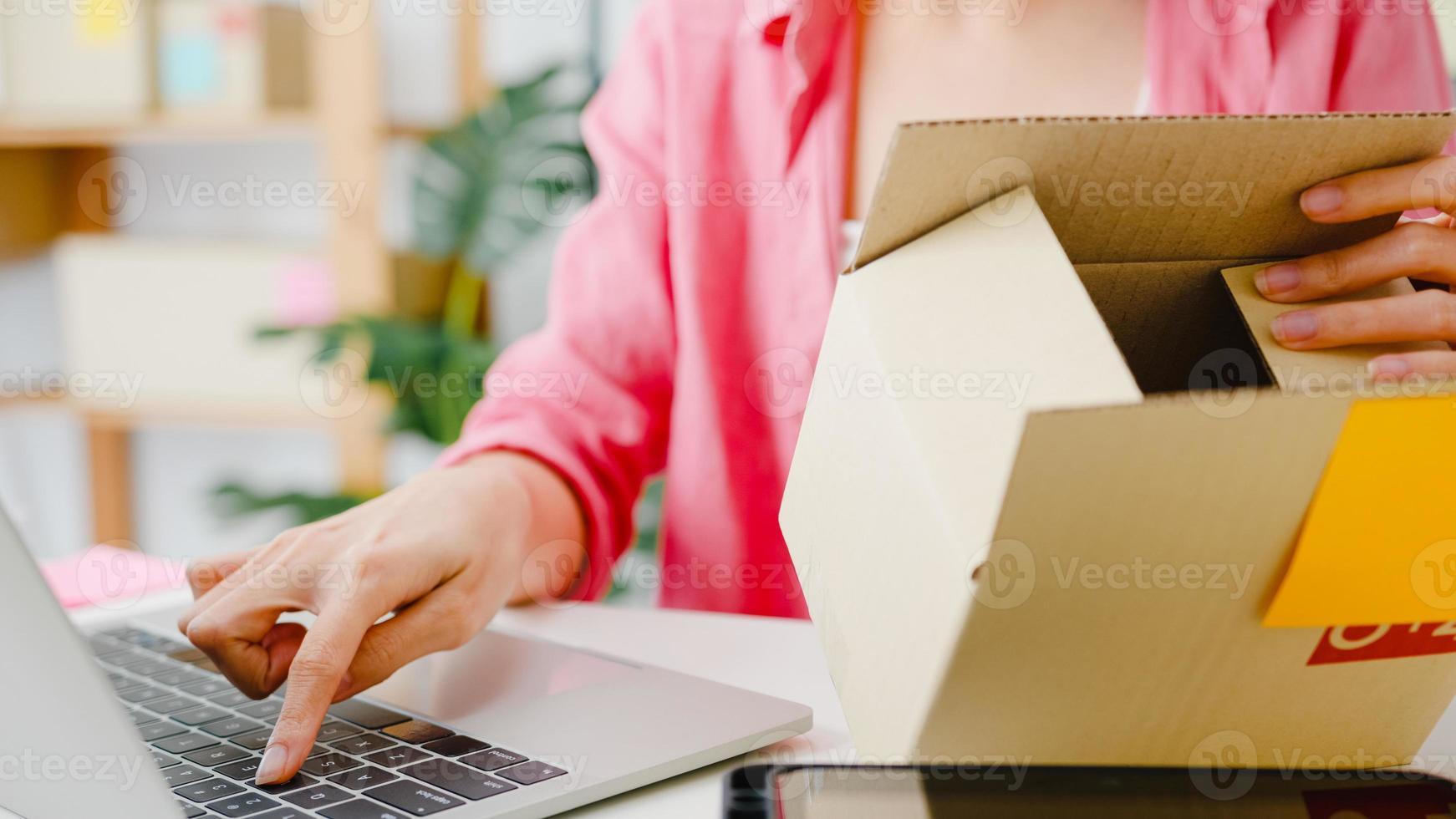 ung asien entreprenör affärskvinna kontrollera produkt inköpsorder på lager och spara till dator laptop arbete på hemmakontor. småföretagare, onlinemarknadsleverans, livsstil frilansande koncept. foto