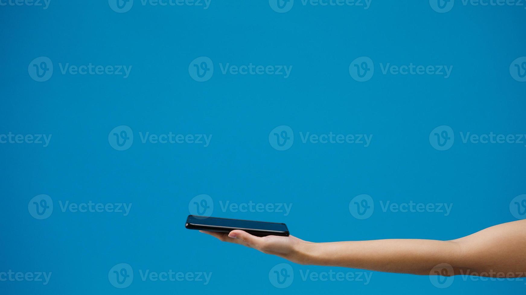ung flicka som handlar online med mobil och betalningsorder online isolerad över blå bakgrund. kopiera utrymme för att placera en text, meddelande för annons. reklamområde, mockup -reklaminnehåll. foto