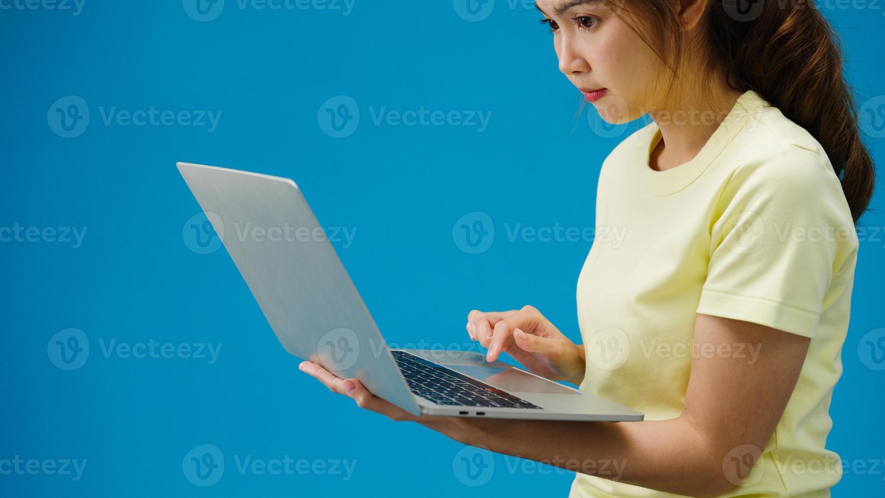 ung flicka som handlar online med bärbar dator och betalningsorder online isolerad över blå bakgrund. kopiera utrymme för att placera en text, meddelande för annons. reklamområde, mockup -reklaminnehåll. foto