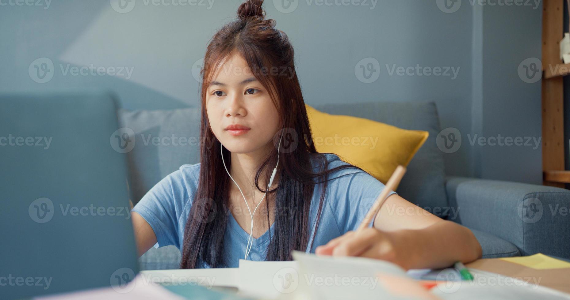 ung asiatisk tjej tonåring med slitage hörlurar använda bärbar dator lära sig online skriva föreläsning anteckningsbok i vardagsrummet hemma. isolera utbildning online e-learning coronavirus-pandemikoncept. foto