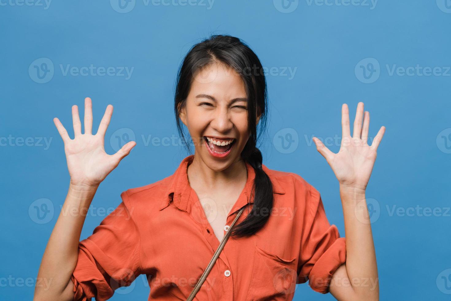 ung asiatisk dam känner lycka med positivt uttryck, glädjande överraskning funky, klädd i avslappnad trasa och tittar på kameran isolerad på blå bakgrund. glad förtjusande glad kvinna jublar över framgång. foto