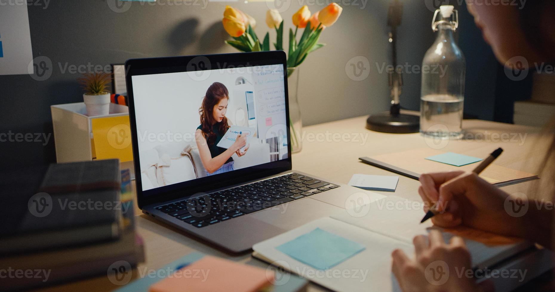 ung asien tonåring flicka student distansundervisning lektion med online -lärare och studera på bärbar skärm i vardagsrummet hemma natten. på distans, social distansering, karantän för förebyggande av corona -virus. foto