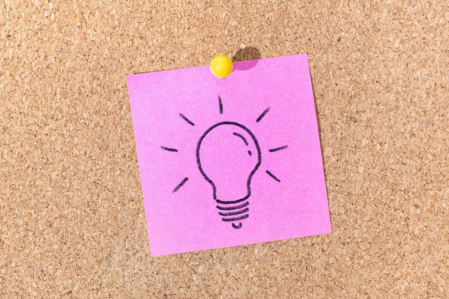 ljus idé eller kreativt processkoncept. glödlampa ritning på klisterlapp på korkbräda foto