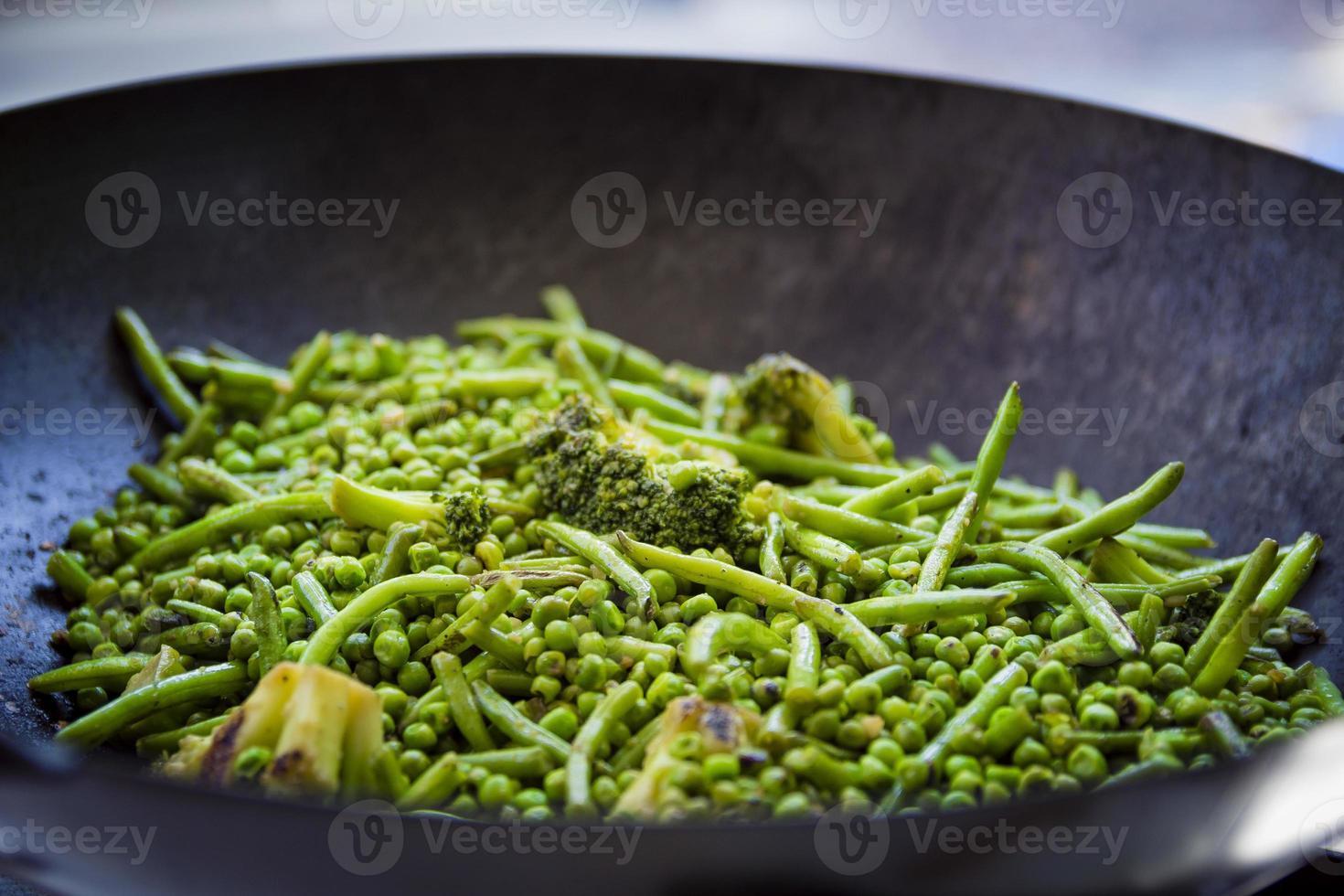 närbild på gröna bönor, broccoli och ärtor tillagas i en stor järnpanna foto