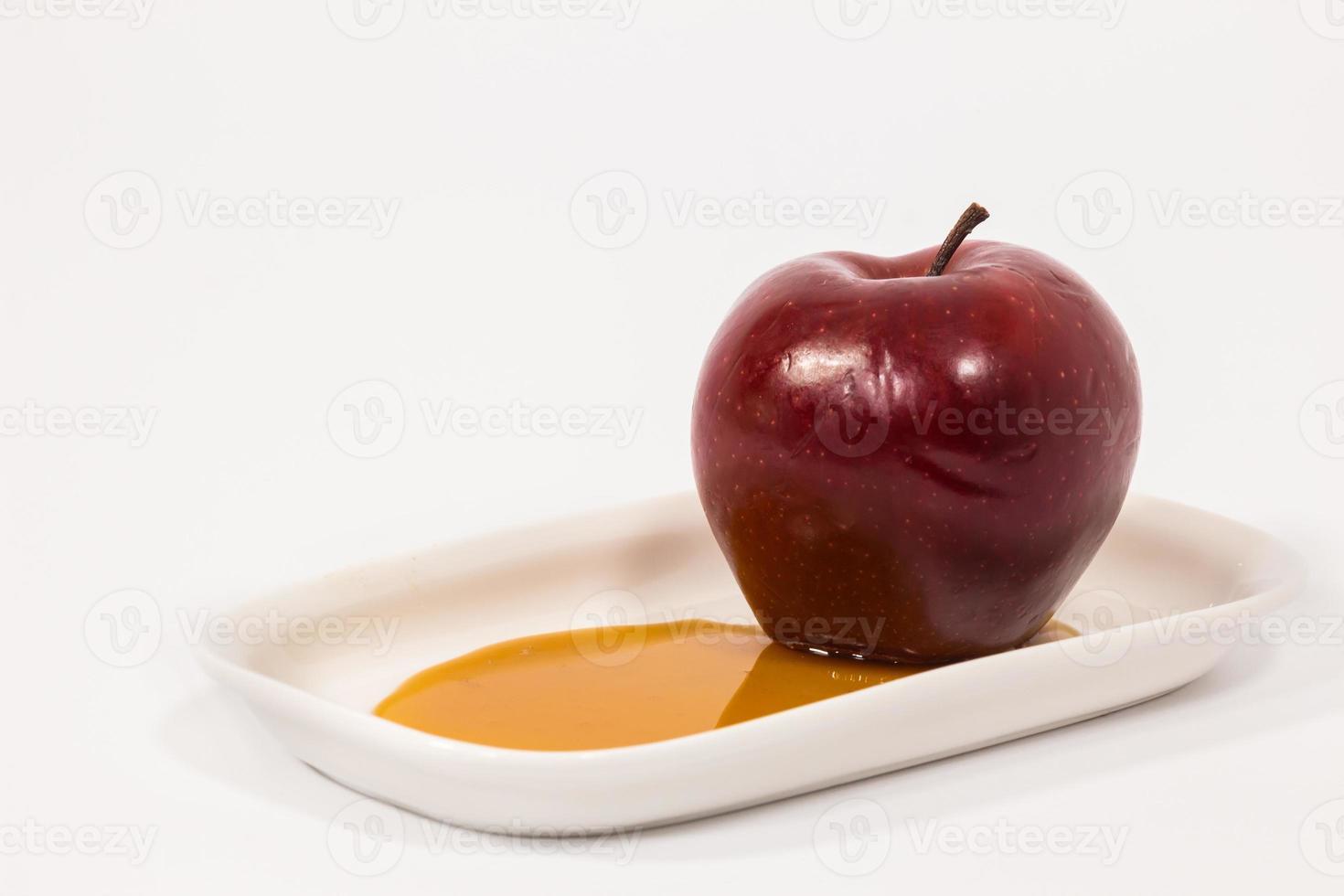 rött äpple på vit tallrik med honung isolerad på en vit bakgrund foto