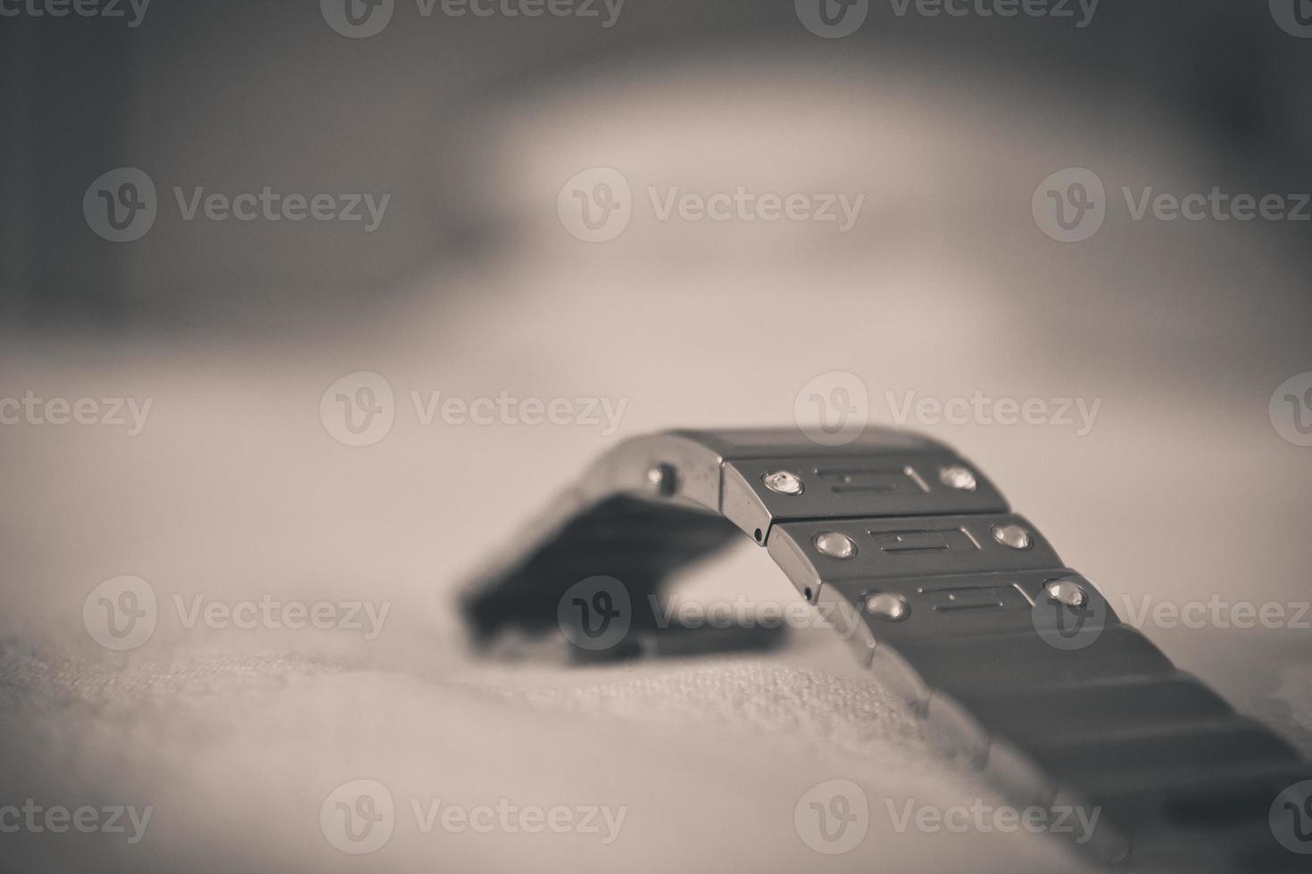 närbild av ett klockarmband av metall är på en vit trasa. vita stenar inbäddade i klockarmbandet. suddig bakgrund. foto