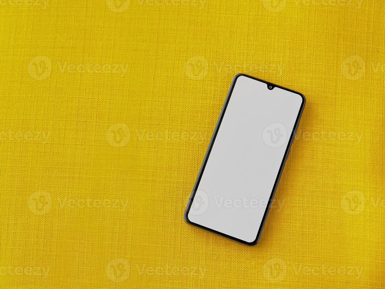 svart mobil smartphone -mockup ligger på ytan med en tom skärm isolerad på en gul tygbakgrund foto