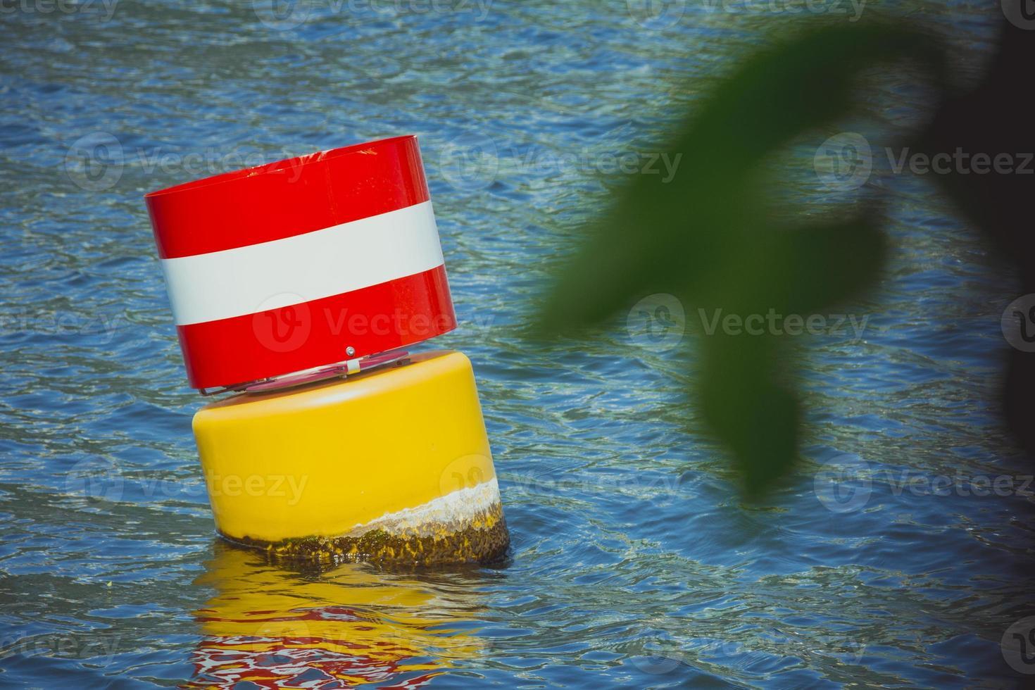 gul röd och vitt stål navigerande flytande boj i det blå havsvattnet foto
