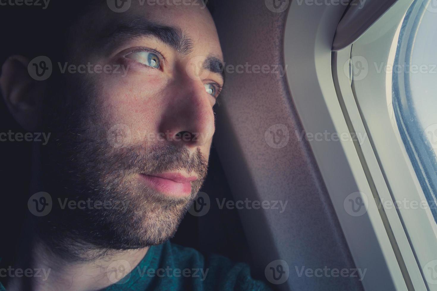 närbild av en fundersam man som tittar utanför genom fönstret på ett flygplan foto