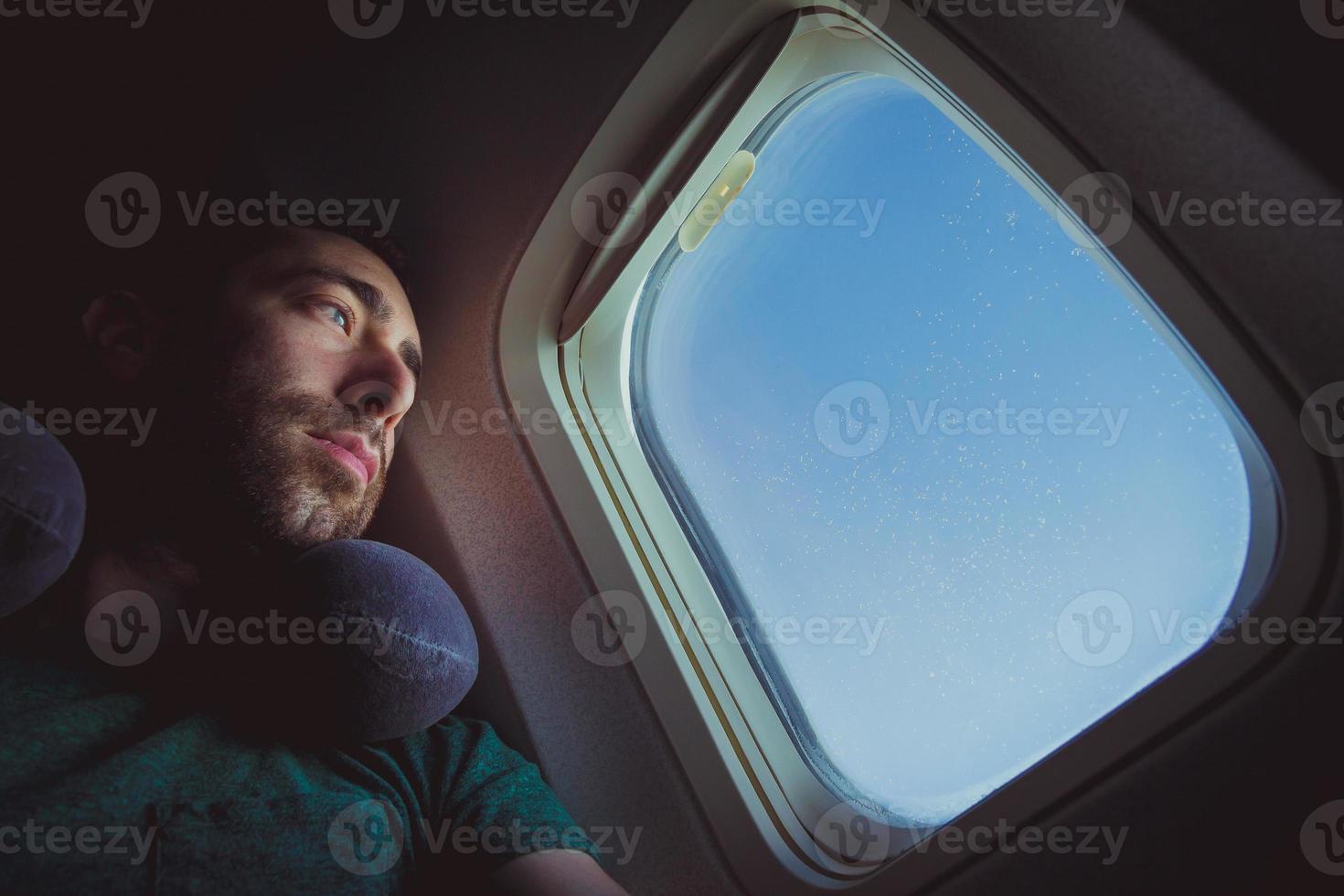 fundersam man med nackkudde som tittar ut genom fönstret på ett flygplan foto
