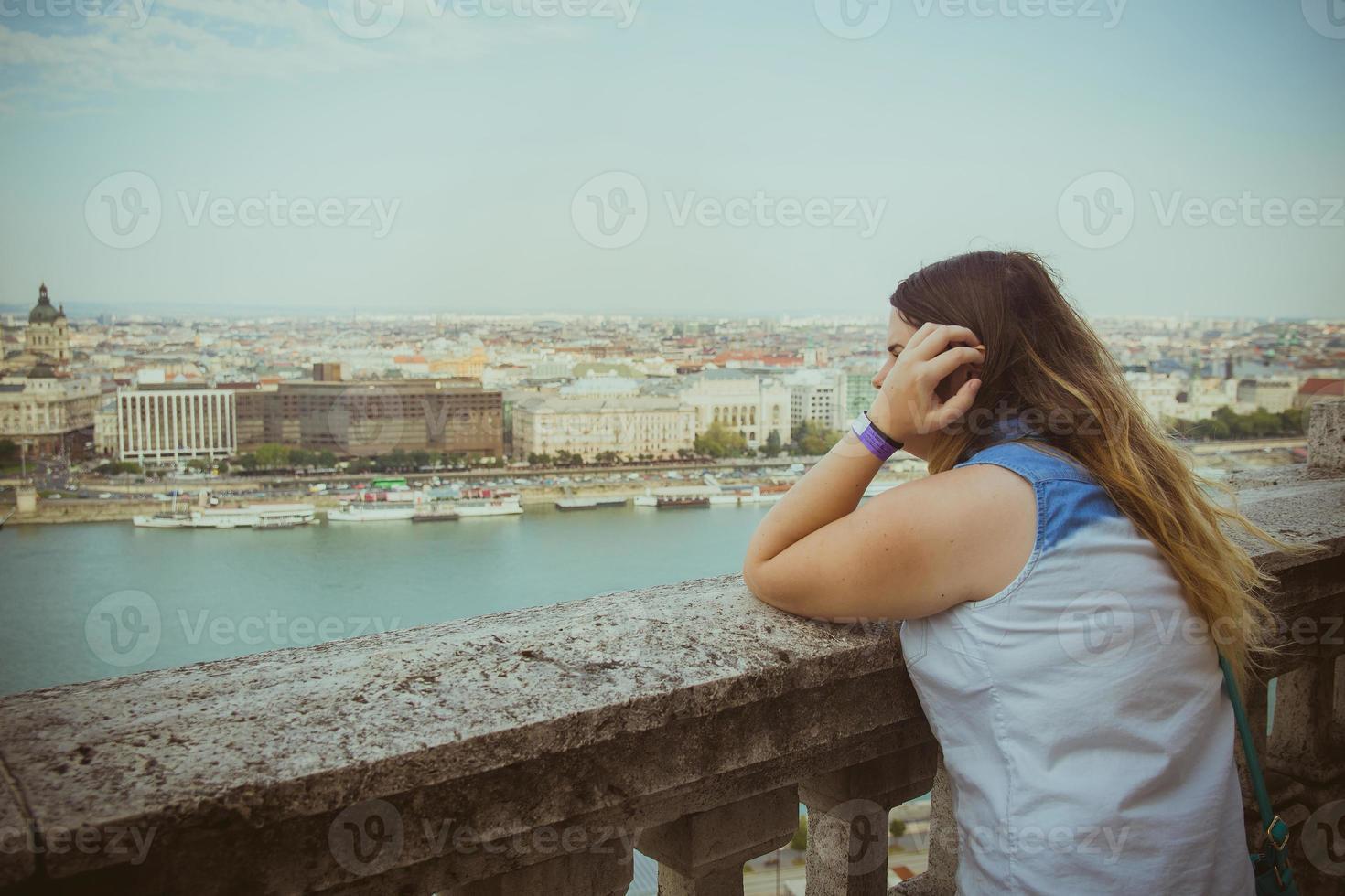kvinna lutar sig på räcket och tittar ut mot havet vid horisonten foto