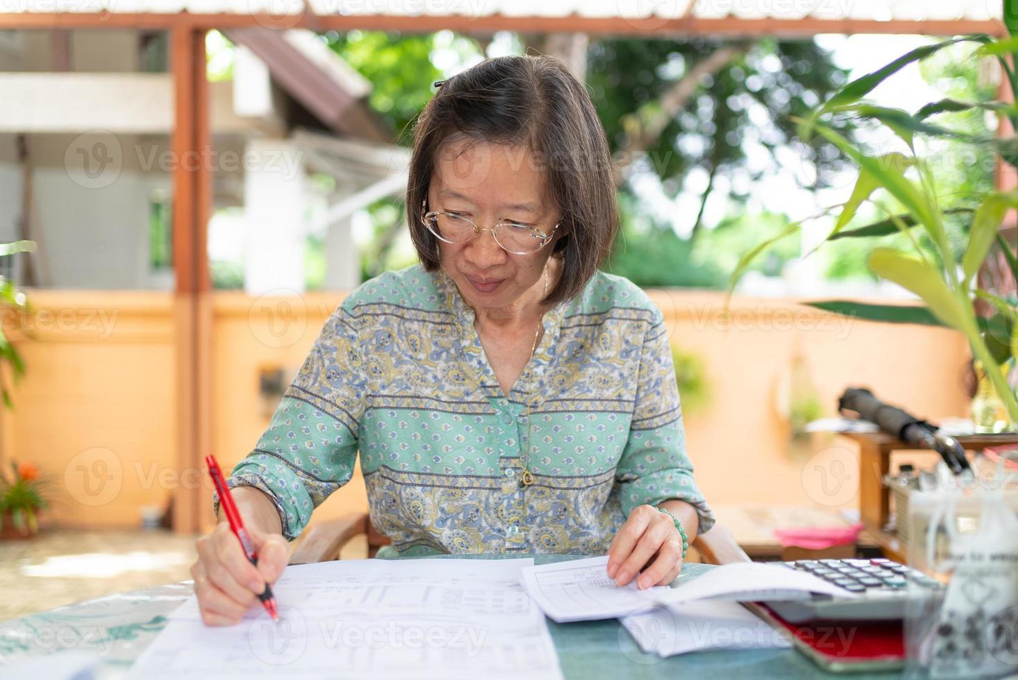 senior asiatisk kvinna beräknar inkomst- och kostnadsbalans på hemterrassen foto