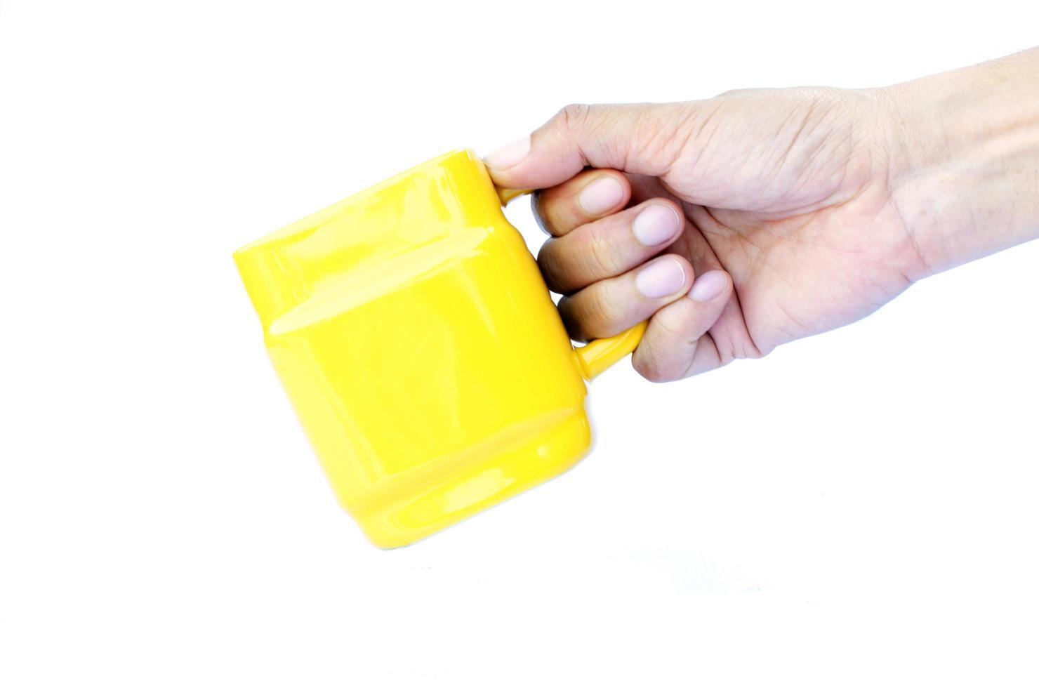 höger hand som håller gula koppar isolerade på vit bakgrund foto