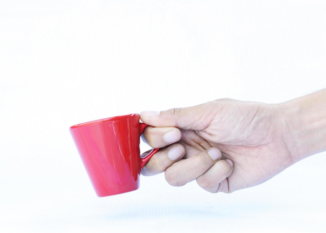 hand som håller röda koppar isolerade på vit bakgrund foto